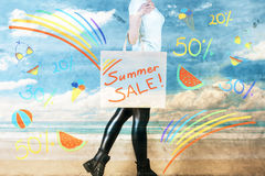 Sales concept. Side view of young woman at the beach holding shopping bag with summer sale text and other drawings. Sales concept Stock Photo