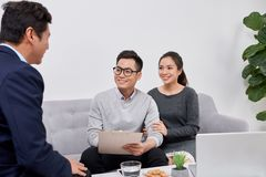 Sales Consultant showing new investment plans to young asian couple stock images