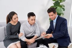 Sales Consultant showing new investment plans to young asian couple stock photos