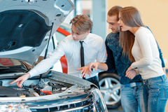 Sales consultant shows technical characteristics. Really powerful and fuel efficient engine. Sales consultant pointing to the engine of the vehicle describes Royalty Free Stock Photos