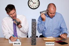 Sales and despatch department. Amusing photo showing the behind the scenes reality of the sales and despatch departments for a small business, both guys sharing Royalty Free Stock Images