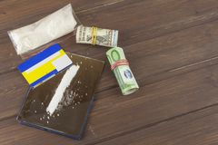 Sales of drugs. International crime, drug trafficking. Drugs and money on a wooden table. Stock Photo