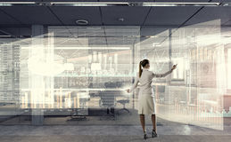 Sales dynamics report  . Mixed media. Elegant businesswoman in modern office drawing infographs Stock Photo