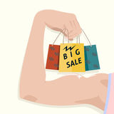 Sales force. Women's muscular arm holding shopping bags. Big sale