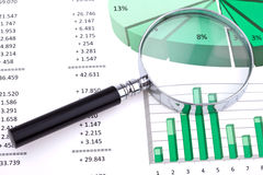 Sales forecasts. An image of business accounts and statistics with a hand magnifier focusing on one market sector Stock Images