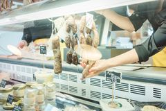 Sales girl in deli at the meat counter cutting some sausages. Sales girl in deli or supermarket at the meat counter cutting some sausages royalty free stock photos