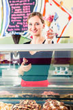 Sales girl handing wafer of ice cream over counter. Ice-cream seller portion a scoop of ice cream to wafer in parlor counter or cafe royalty free stock photography