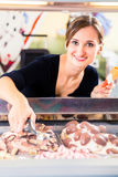 Sales girl portion s scoop  of ice cream to wafer Stock Photography