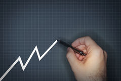 Sales going up. Hand drawing upward line on graph stock photo