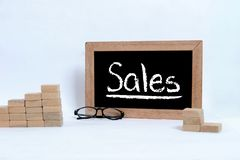 SALES inscription on blackboard. Eye glasses and Wood block stacking as step stair stock images
