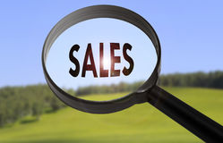 Sales. Magnifying glass with the word sales on blurred nature background. Searching sales concept Royalty Free Stock Photo