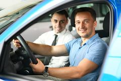Sales man with client are sitting in new car royalty free stock images