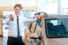 Sales man holds keys from a new car Stock Photography