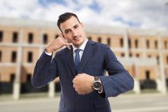 Sales man or realtor making call me you are late gesture. Sales man or realtor making call me you are late for meeting gesture on new under construction bricks stock image