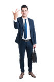 Sales man standing holding briefcase and showing number three Stock Photo