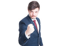 Sales man wearing suit showing fist like fighting. Being mad isolated on white background with copy text space Stock Photo