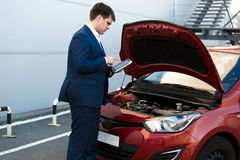 Sales manager making photo under car bonnet Royalty Free Stock Photo
