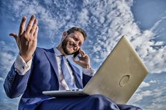 Sales manager responsibilities. Stay in touch. Man formal suit work with laptop while speak on phone. Businessman royalty free stock image