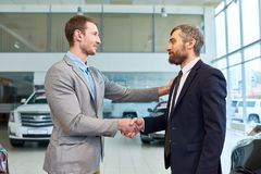 Sales Manager Shaking Hands with Client Buying Car. Waist up portrait of  handsome young manager shaking hands with mature client in car showroom, after selling Royalty Free Stock Image