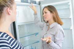 Sales manager showing fridge to female client in appliances shop royalty free stock image