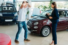 Sales manager showing to happy and surprised customer a car. He won stock photography