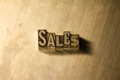 Sales - Metal letterpress lettering sign. Lead metal 'Sales' typography text on wooden background Royalty Free Stock Image