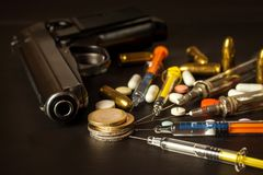 Sales of narcotics. Weapon and drugs on the table. Handgun and ammunition. Stock Image