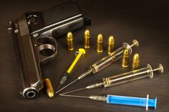 Sales of narcotics. Weapon and drugs on the table. Handgun and ammunition. Royalty Free Stock Image