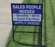 Sales People Needed Employment Sign. An employer advertising a sales position for employing, promising great benefits, 401K and a great pay plan Royalty Free Stock Images