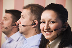 Sales people representative. Three people sales representative working in office,focus on woman smiling,men standing in profile with headset.Check also,for Royalty Free Stock Photography