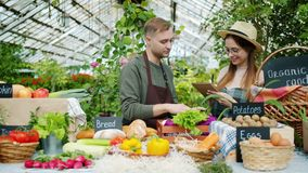 Sales people man and woman talking during organic food sale in greenhouse. Sales people young man and woman are talking during organic food sale in greenhouse stock footage