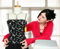 Sales Person. Young woman at cash register adjusting dress on mannequin Royalty Free Stock Photos