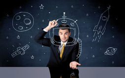 Sales person drawing helmet and space rocket Royalty Free Stock Image