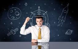 Sales person drawing helmet and space rocket Royalty Free Stock Photos