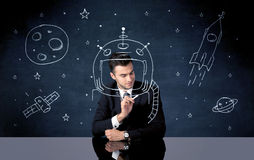 Sales person drawing helmet and space rocket Stock Photo