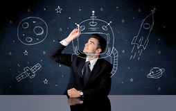 Sales person drawing helmet and space rocket Stock Images