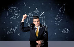 Sales person drawing helmet and space rocket. A young happy businessman in elegant suit drawing helmet, satellite and rocket in empty space with a chalk royalty free stock photos