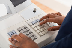 Sales Person Entering Amount On Cash Register Royalty Free Stock Image