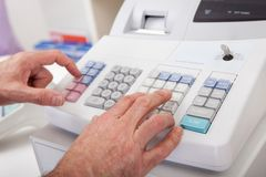 Sales person entering amount on cash register Royalty Free Stock Photo