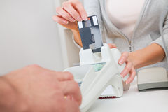 Sales person inserting card into scanner Stock Image