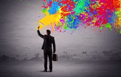 Sales person painting colorful splatter. An elegant businessman in suit painting colorful splatter, bright colors on grey urban wall with a paint roller in his Royalty Free Stock Photos