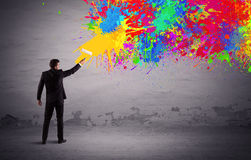 Sales person painting colorful splatter. An elegant businessman in suit painting colorful splatter, bright colors on grey urban wall with a paint roller in his Stock Photography