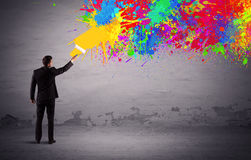 Sales person painting colorful splatter. An elegant businessman in suit painting colorful splatter, bright colors on grey urban wall with a paint roller in his Royalty Free Stock Photo