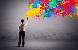 Sales person painting colorful splatter. An elegant businessman in suit painting colorful splatter, bright colors on grey urban wall with a paint roller in his Stock Image