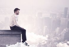 Sales person sitting on building edge in city royalty free stock photo