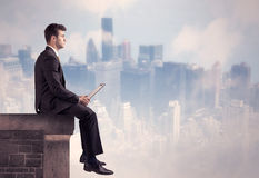 Sales person sitting on top of a tall building Stock Image