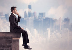Sales person sitting on top of a tall building Stock Photography