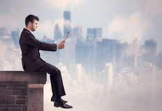 Sales person sitting on top of a tall building Stock Photo