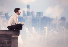 Sales person sitting on top of a tall building Royalty Free Stock Image