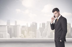 Sales person talking in front of city scape. A young adult businessman standing in front of city landscape with skyscraper buildings and clouds concept Royalty Free Stock Photography